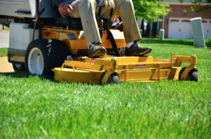 Image of lawn care guy mowing grass with a proffessional mower.